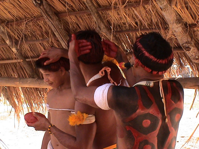 Men prepairing themselves for a dance in the central ('men's') hut