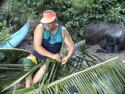Woman plaiting coconut leaves