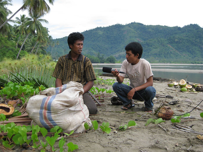 Winarno interviewing a coconut farmer on his work